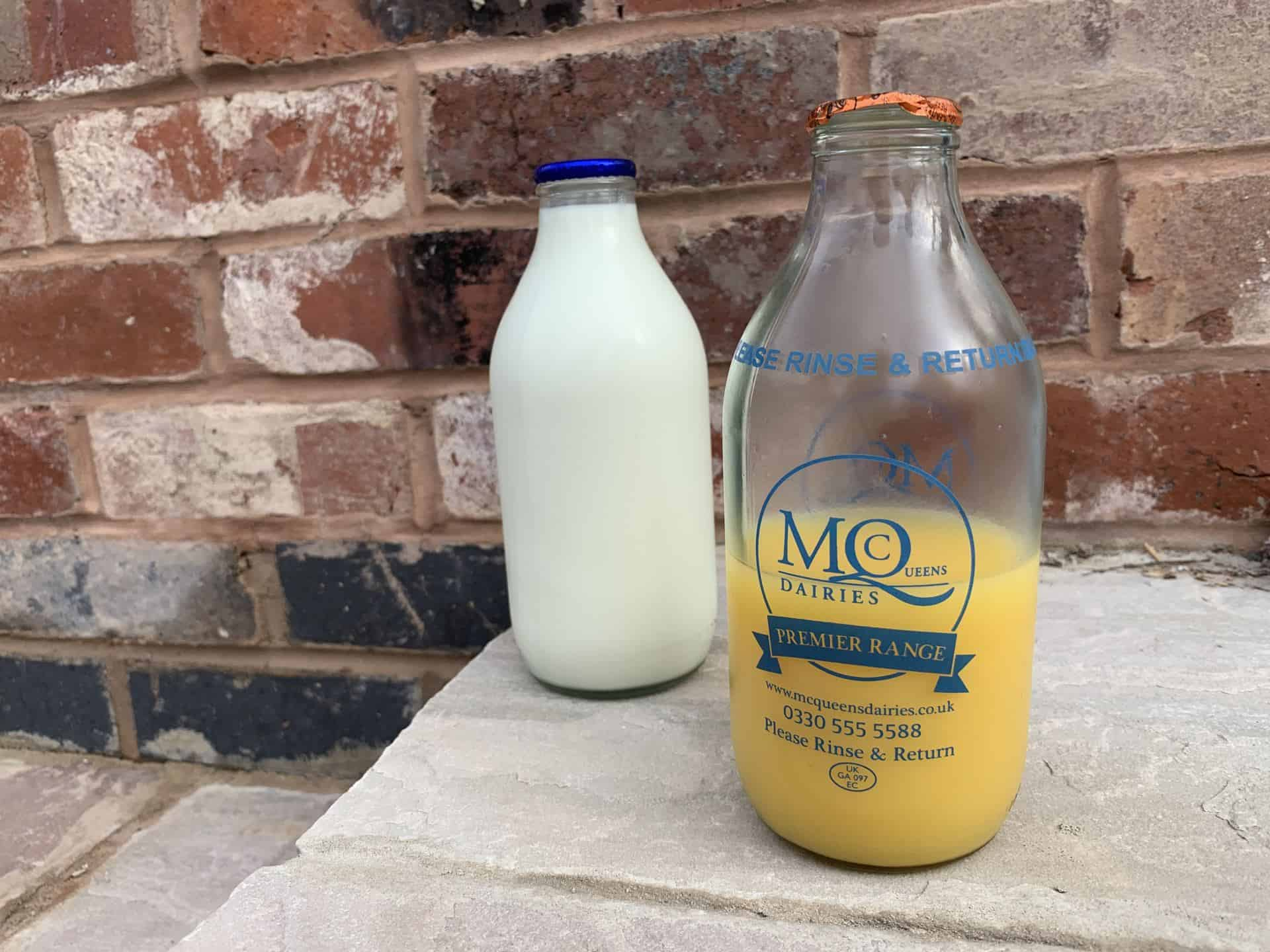 Bottled milk and orange on a doorstep